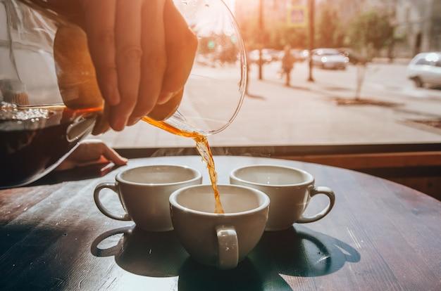 Camarero vierte café en tazas