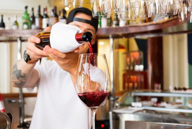 Camarero vierte una copa de vino tinto en el bar