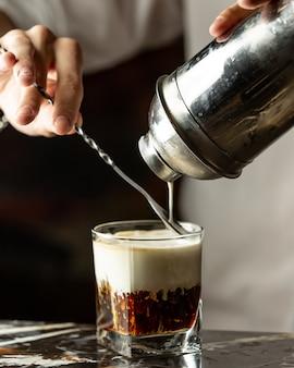 Camarero vierte crema en café helado con la ayuda de la cuchara