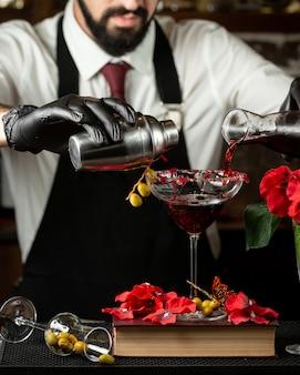 Camarero vierte la mezcla de cóctel en un vaso