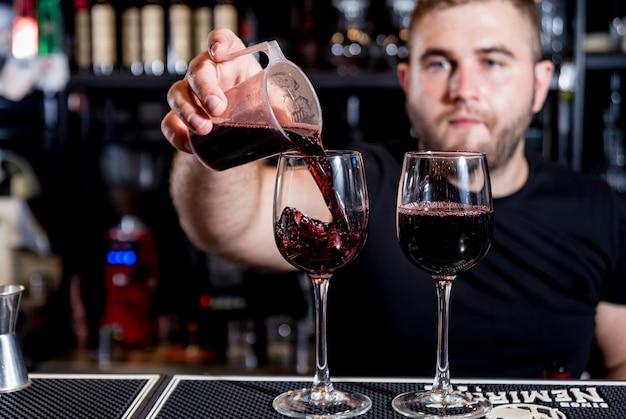 Camarero vierte vino tinto en un vaso. sumiller. restaurante. la vida nocturna