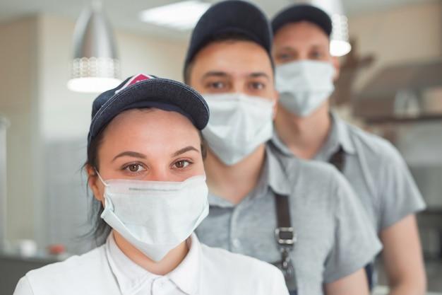 Camareros con máscaras y sombreros médicos.