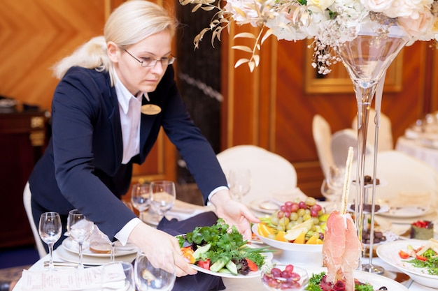 Los camareros ponen las mesas en el restaurante para el banquete.