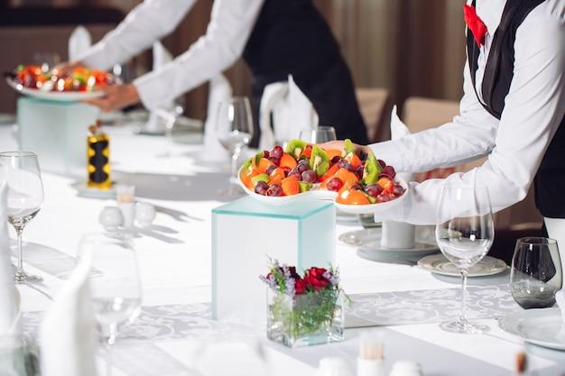 Camareros sirviendo mesa en el restaurante preparándose para recibir invitados.