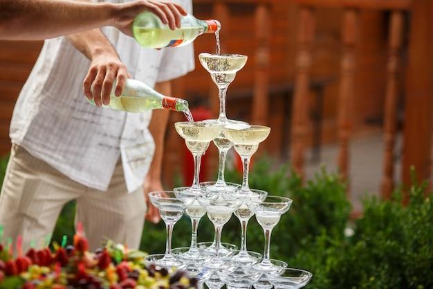 Los camareros vierten champán en una pirámide de copas de vino