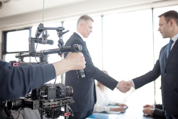 Camarógrafo con cámara firme, haciendo un video de gente de negocios dándose la mano