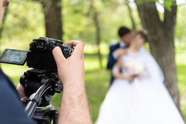 El camarógrafo dispara a los casados en el jardín en el verano.