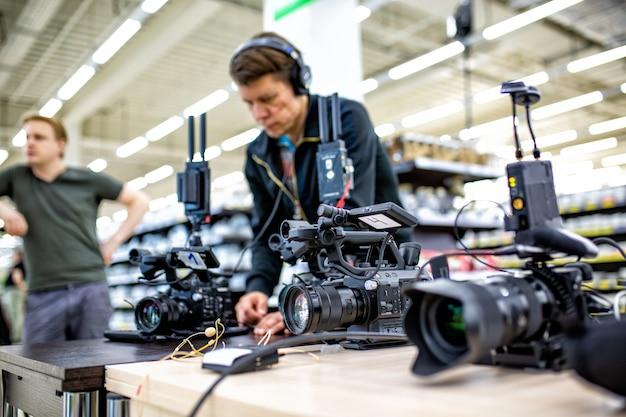 Camarógrafo filmando una película o un programa de televisión en un estudio con una cámara profesional, detrás del escenario