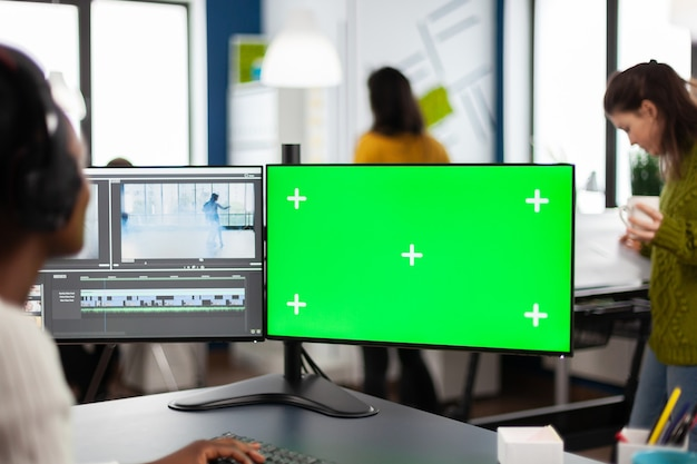 Camarógrafo de mujer africana con montaje de película de procesamiento de auriculares trabajando en pantalla verde, pantalla aislada chroma key de la computadora