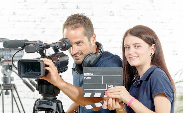 Un camarógrafo y una mujer joven con una cámara de cine y badajo