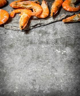 Camarón grande crudo en mesa de piedra.