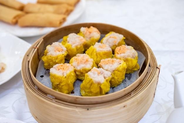 Camarones albóndigas amarillas. dim sum establecido. en bandeja de bambú sobre mesa