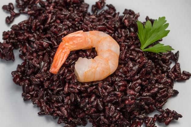 Camarones con arroz negro. hoja de perejil. de cerca. vista superior