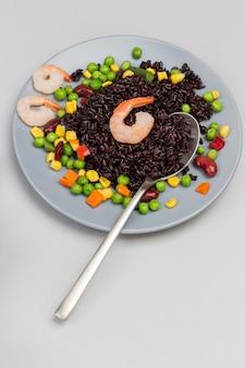 Camarones con arroz negro, verduras y cuchara sobre placa gris. vista superior