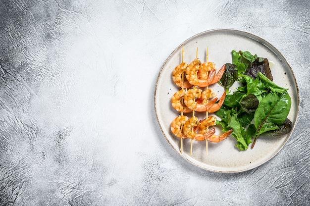Camarones asados langostinos en brochetas con ensalada de espinacas