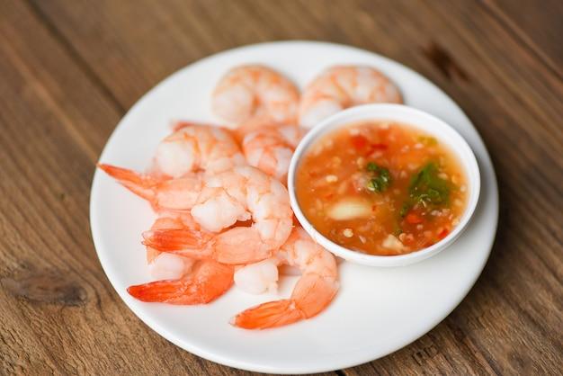 Camarones deliciosos condimentos especias en plato blanco apetitosas gambas cocidas gambas cocidas, ensalada salsa de mariscos de estantería