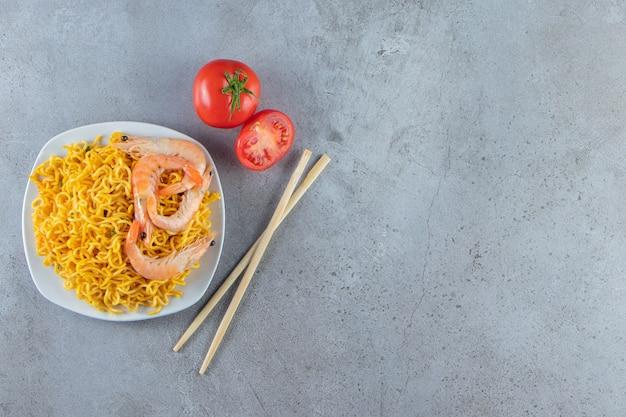 Camarones y fideos en un plato, sobre el fondo de mármol.