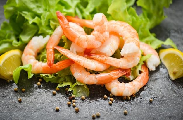 Camarones frescos langostinos pelados langostinos cocidos especias ensalada de vegetales con limón lechuga o roble verde