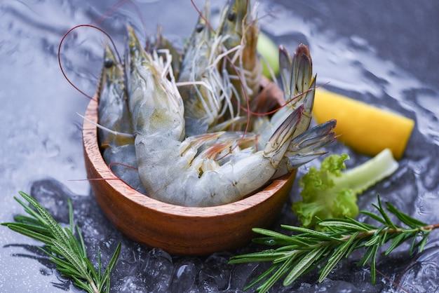 Camarones frescos en un tazón con ingredientes de romero, hierbas y especias para cocinar mariscos - camarones crudos, gambas sobre hielo congeladas en el restaurante de mariscos