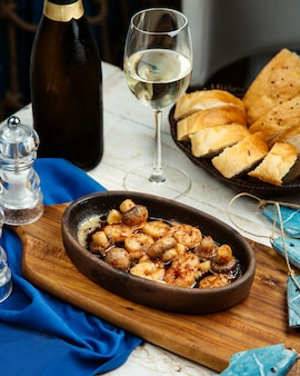 Camarones fritos y champiñones servidos con pan y vino blanco