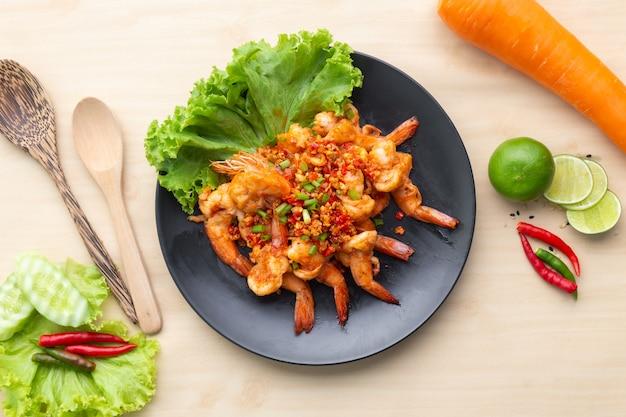 Camarones fritos con pimienta y sal en placa negra sobre mesa de madera