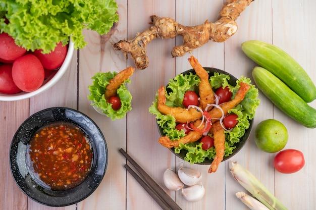 Camarones fritos rebozados en ensalada y tomates en un tazón de madera.