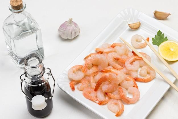 Camarones con limón en plato blanco. salsa de soja y agua en botellas de vidrio. vista superior