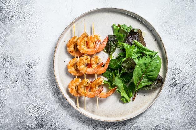 Camarones a la parrilla, brochetas de langostinos con hierbas, ajo, brocheta de kebab. fondo gris