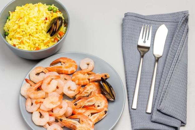 Camarones en placa gris. mejillones con arroz en cuenco gris. cuchara y tenedor sobre una servilleta gris. vista superior.