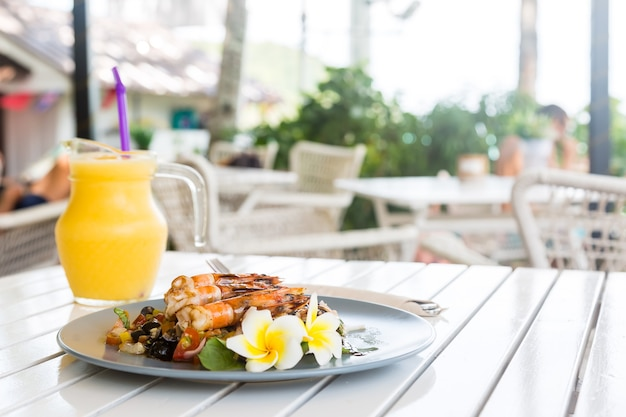 Camarones a la plancha o langostinos con verduras fritas en plato azul decorado con flor de frangipani