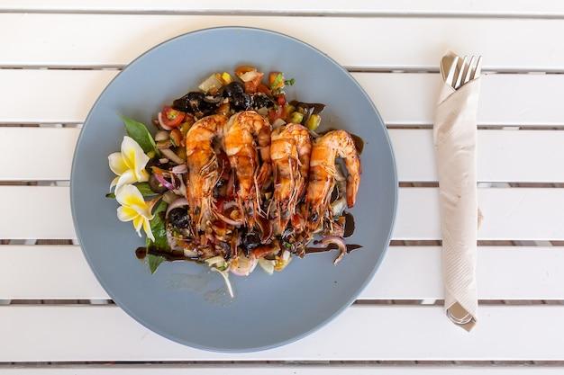 Camarones a la plancha o langostinos con verduras fritas en el plato celeste con flor de frangipani
