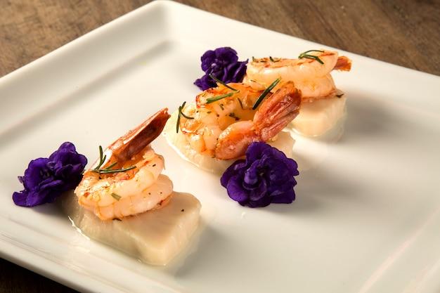 Camarones a la plancha con pescado crudo de uñas en un plato blanco en la mesa