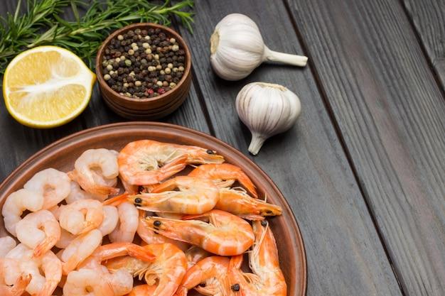 Camarones en plato de cerámica. ramitas de pimienta de jamaica, limón, ajo y romero en la mesa. endecha plana