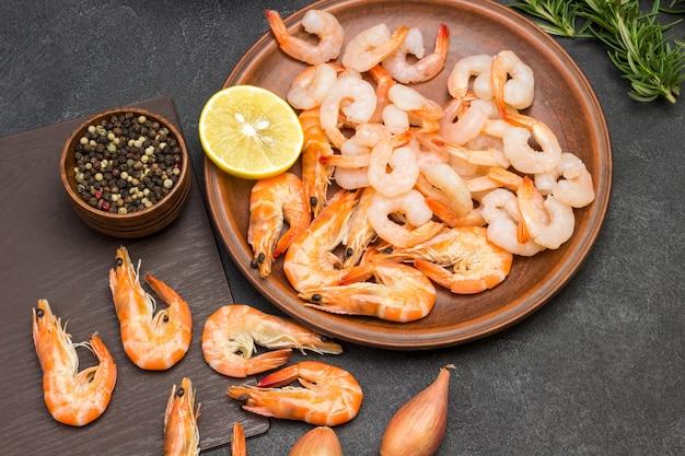 Camarones en plato de cerámica. ramitas de pimienta de jamaica y romero en la mesa. endecha plana