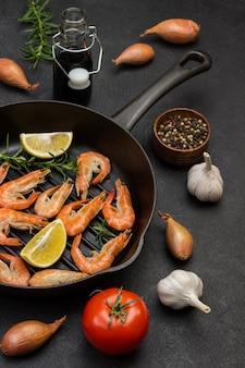 Camarones con ramitas de romero y limón en sartén. tomate, ajo y cebolla en mesa. vista superior