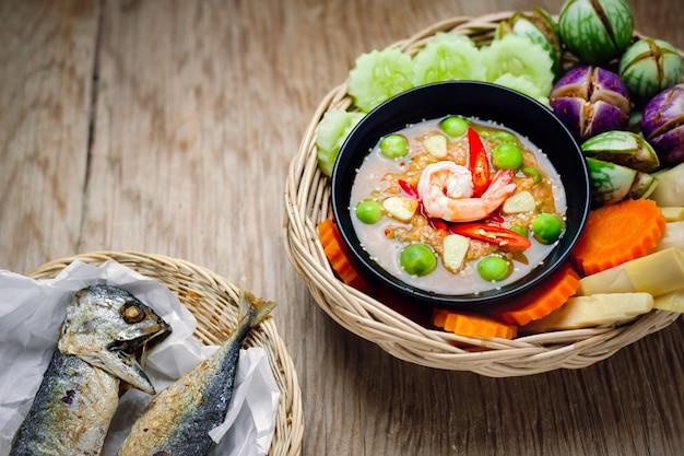Camarones - salsa de pasta con verduras, tortilla, caballa frita en la mesa de madera.