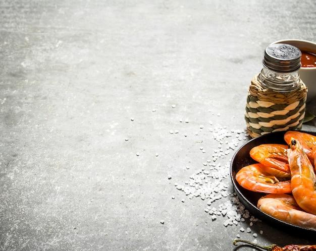 Camarones en sartén con salsa sobre mesa de piedra.