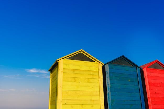 Cambiadores de cabañas para bañistas en una playa del mediterráneo en verano, de color azul, amarillo y rojo.