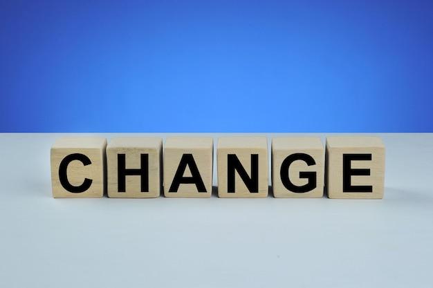 Cambiar palabra cubo en madera, concepto de negocio aislado sobre fondo azul.
