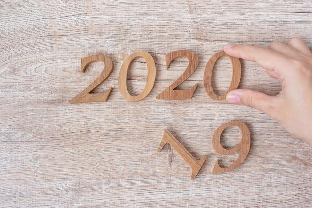 Cambie a mano el número de 2019 a 2020 en madera. resolución