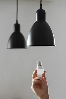Cambio de bombilla por bombilla led en lámpara de pie en color negro. sobre fondo gris claro.