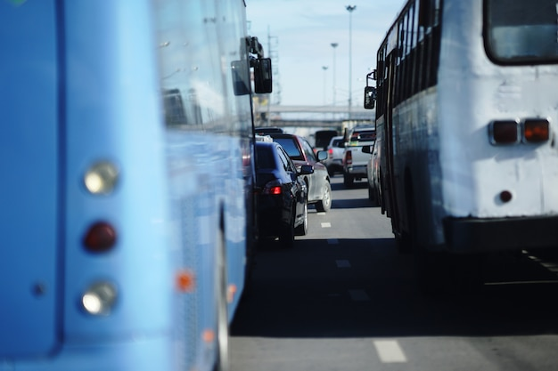 Cambio de carril de minitruck en carretera de tráfico lleno de gente en la hora pico vista entre autobuses