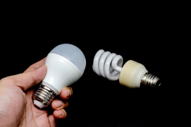 Cambio de bombilla fluorescente twister a led, mano que sostiene la bombilla led