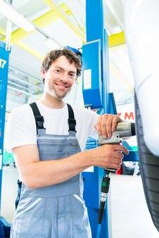 Cambio mecánico de neumáticos en taller de coches.