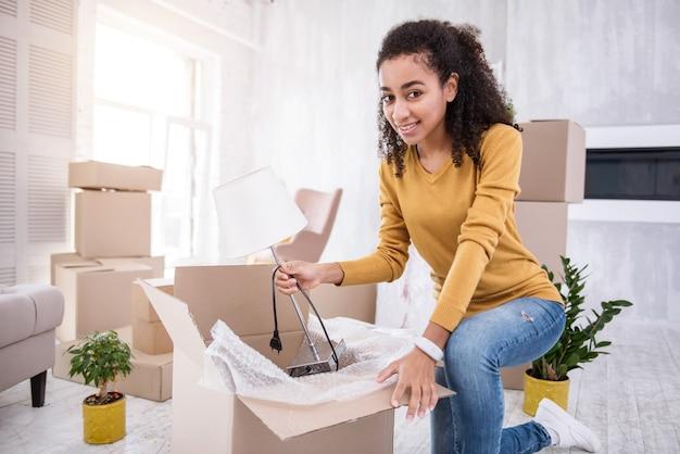 Cambio de piso. alegre niña rizada sonriendo a la cámara y poniendo una lámpara blanca en la caja mientras empaca cosas antes de mudarse del piso