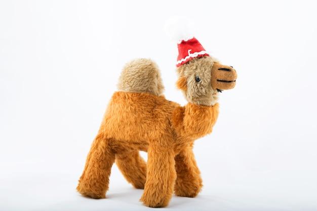 Camello de peluche con sombrero de santa claus sobre un fondo blanco. de cerca