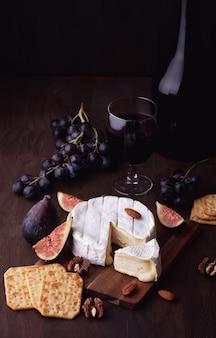 Camembert de queso francés con copa de vino tinto, uvas e higos