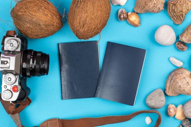 Cameracoconuts conchas y documentos sobre un fondo azul para el viajero