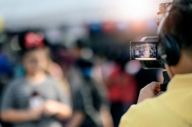 Cameraman grabando video de mujer joven, foco en pantalla de cámara.