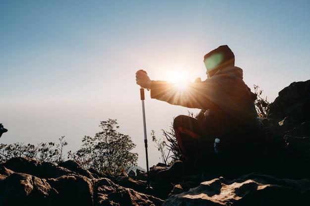 Caminando al hombre en la montaña de la silueta de la puesta del sol con concepto de la aventura de la forma de vida del viaje.